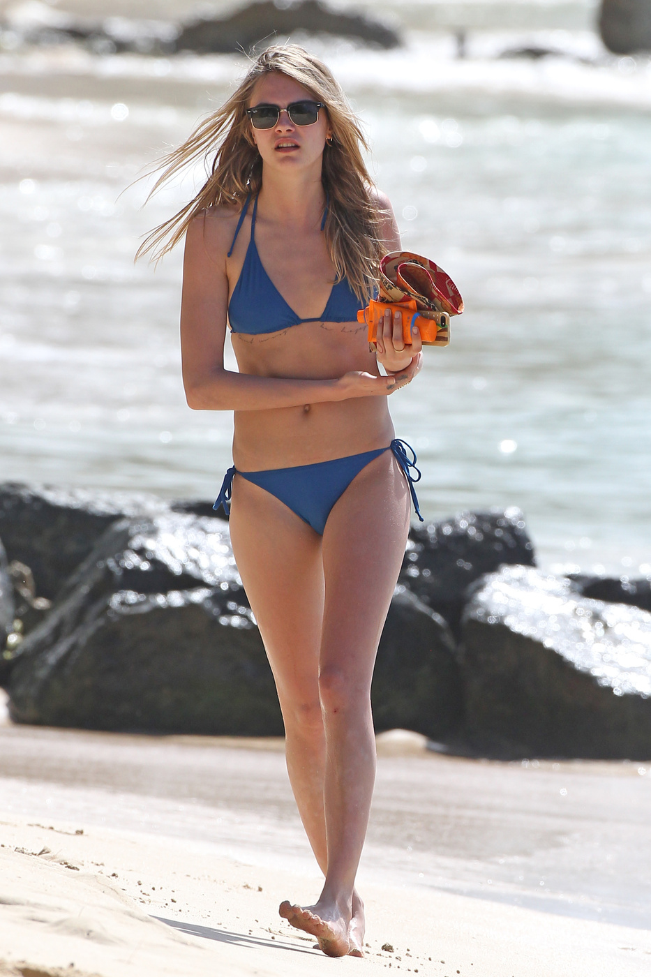 Cara Delevingne opts for some sunbathing on a boat while her friends do some water sports in Barbados