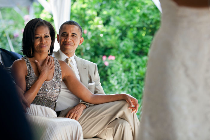 """June 18, 2012 """"The First Lady reacts as she watches Laura Jarrett and Tony Balkissoon take their vows during their wedding at Valerie Jarrett's home in Chicago."""" (Official White House Photo by Pete Souza) This official White House photograph is being made available only for publication by news organizations and/or for personal use printing by the subject(s) of the photograph. The photograph may not be manipulated in any way and may not be used in commercial or political materials, advertisements, emails, products, promotions that in any way suggests approval or endorsement of the President, the First Family, or the White House."""